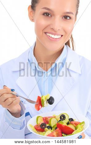 Portrait of a beautiful woman doctor holding a plate with fresh vegetables.