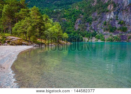 Scenic Glacial Lake in Norway. Crystal Clear Water of the Lake. Rocky Beach.