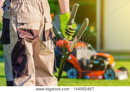 Landscaping Professional. Pro Gardener with Large Scissors and Other Gardening Equipment.