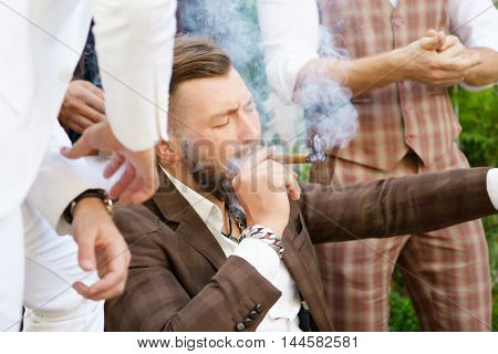 Stylish handsome guy enjoying cigarette with friends