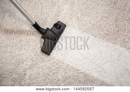 Vacuum cleaner vacuuming dusty carpet