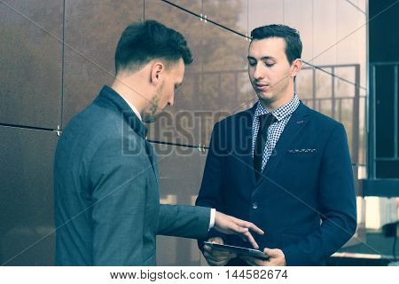 Two young managers talking and looking at a tablet