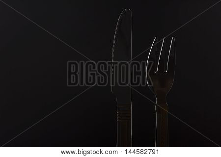 Stainless knife and fork on black background.