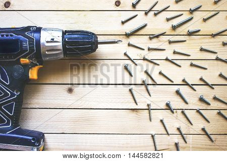Cordless drill on the wooden table with screws