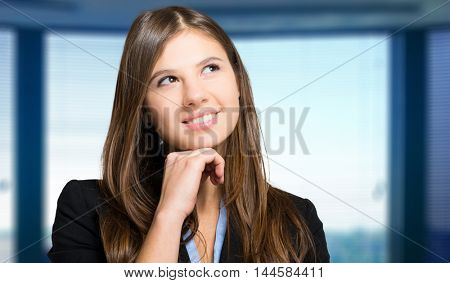 Smiling young female manager thinking at something