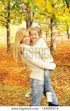 Beautiful smiling mother holding little baby girl, dressed in white knitted sweaters and jeans, autumn outdoor
