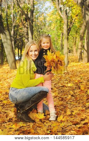 Beautiful young mother and daughter portrait in autumn park with a bouquet of autumn maple leaves