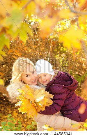 Happy mother and daughter autumn portrait, against sunny autumn park