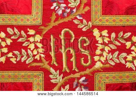 IHS latin letters on an antique vestment chasuble, or Iesus Hominum Salvator, meaning Holy Name of Jesus in Latin