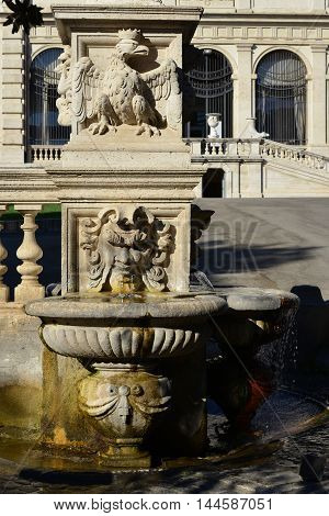 Baroque fountain in Villa Borghese public park with crowned eagle symbol of the ancient noble family