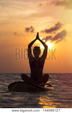 Woman practicing SUP yoga at sunset, meditating on a paddleboard.