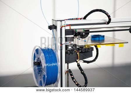 3d printer with blue filament coil close-up. 3d printing process technology