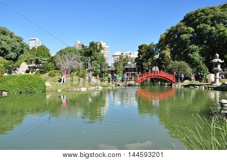 Japanese garden lake with red bridge in a beautiful day