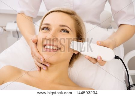 Young beautiful woman applying ultrasound facial skin peeling