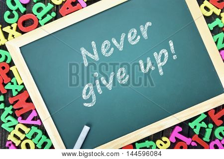 Never give up text on school board and magnetic letters
