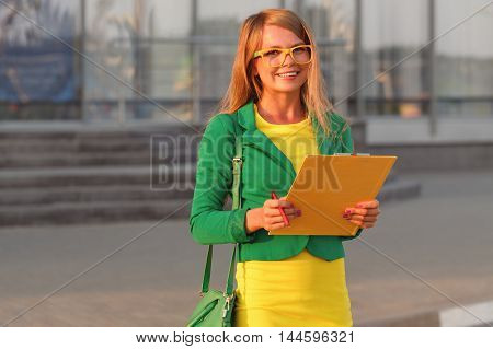 Business woman controls the execution of works. Young attractive girl in glasses and jacket smiles and holding a checklist.