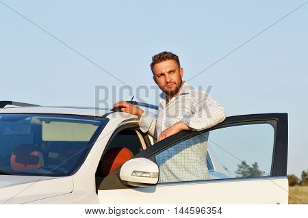 Young handsome man opened the door of his car. He was wearing a shirt in the cage. A man looks into the distance.