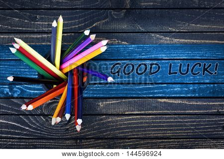Good Luck text painted and group of pencils on wooden table