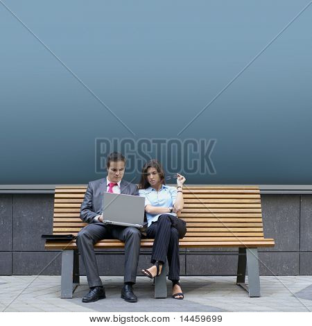 Business couple sitting on the bench