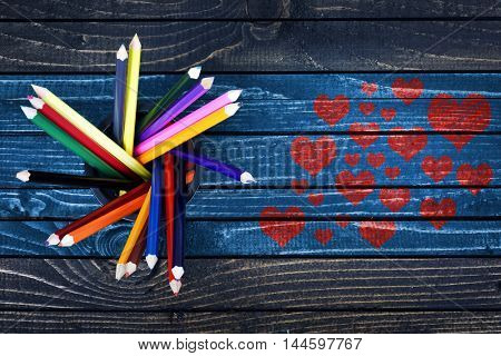 Love concept with many heart shape painted and group of pencils on wooden table