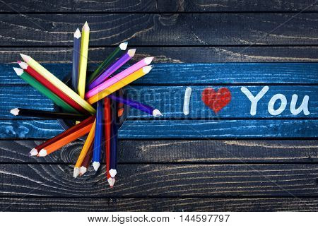 I love you text painted and group of pencils on wooden table