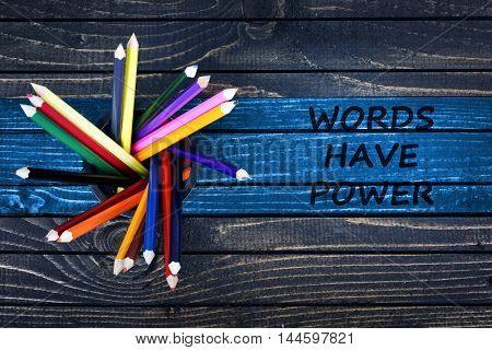 Words have power text painted and group of pencils on wooden table