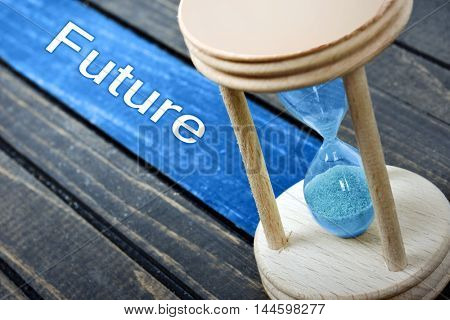 Future text and hourglass on wooden table