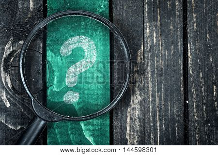 Question Mark painted and magnifying glass on wooden table