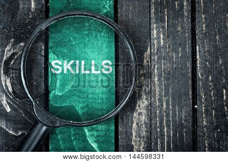 Skills text painted and magnifying glass on wooden table