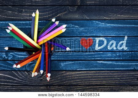 Love Dad text painted and group of pencils on wooden table