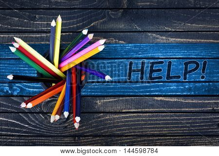 Help text painted and group of pencils on wooden table