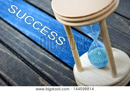 Success text and hourglass on wooden table