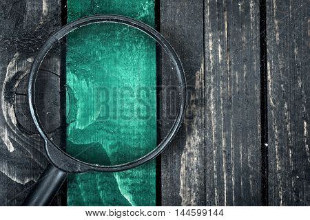 Line painted and magnifying glass on wooden table