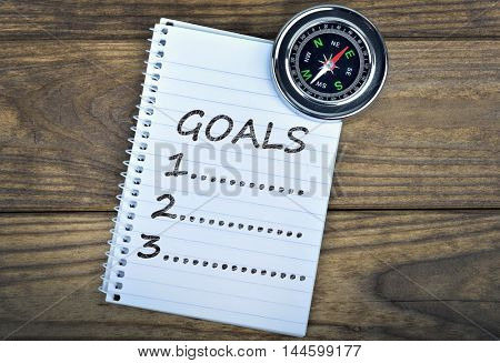 Goals text and metallic compass on wooden table