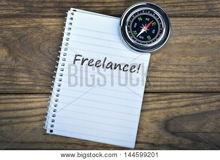 Freelance text and metallic compass on wooden table