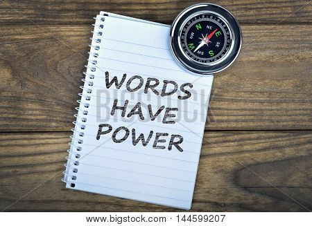 Words have power text and metallic compass on wooden table
