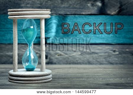 Backup text and hourglass on wooden table