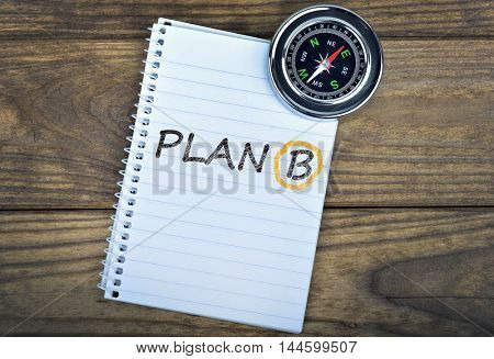 Plan B text and metallic compass on wooden table