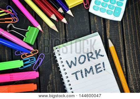 Work Time text on notepad and office tools on wooden table