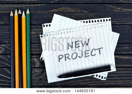 New Project text on notepad and office tools on wooden table