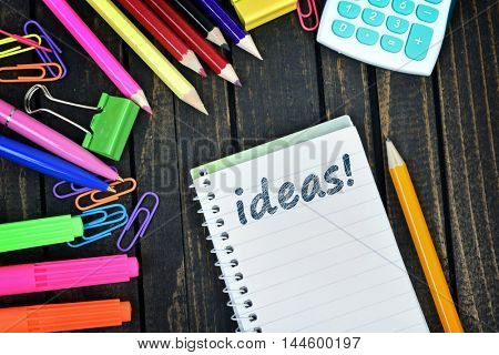 Ideas text on notepad and office tools on wooden table