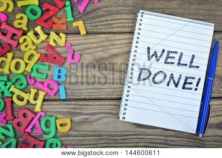 Well Done text on notepad and magnetic letters on wooden table