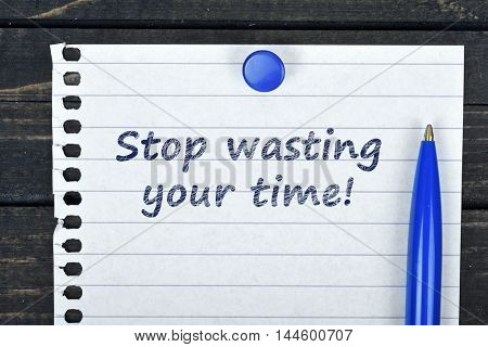 Stop wasting time text on page and pen on wooden table