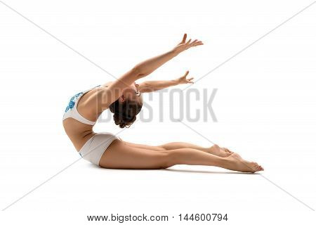 Female gymnast posing while bending her back. Isolated on white