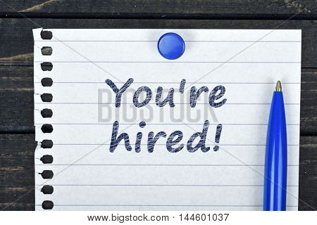 You're hired text on page and pen on wooden table