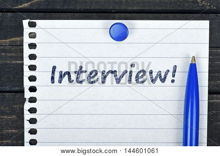 Interview text on page and pen on wooden table