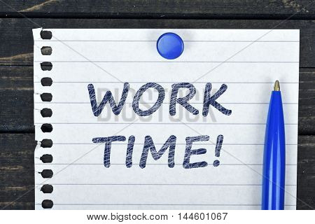 Work Time text on page and pen on wooden table