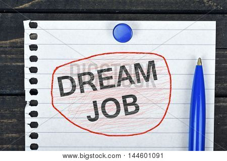 Dream Job text on page and pen on wooden table