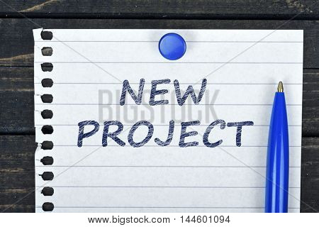 New Project text on page and pen on wooden table