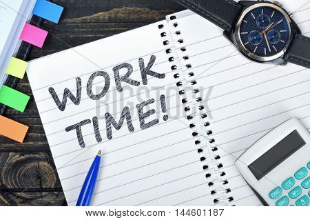 Work time text on notepad and watch on desk